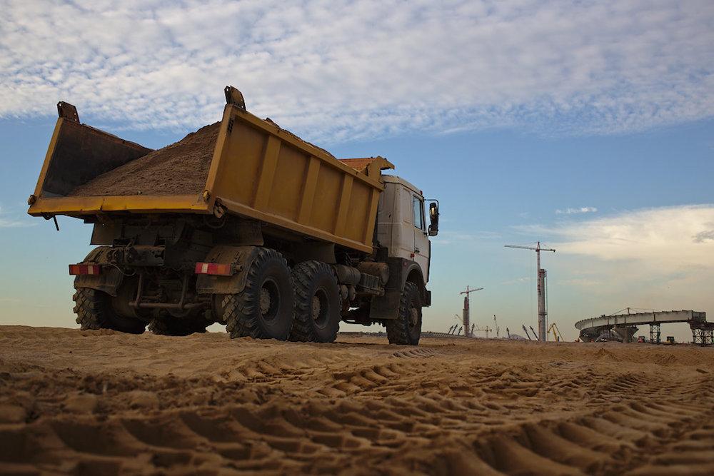 Для ускорения уплотнения грунт проливают и утрамбовывают. В общей сложности здесь уложат несколько миллионов кубометров песка