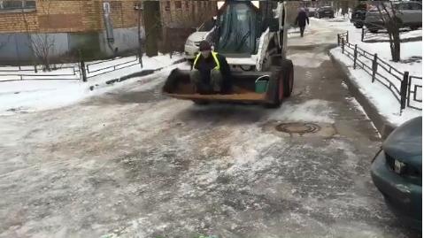 В Петербурге рабочий чистил улицы, забравшись на ковш трактора