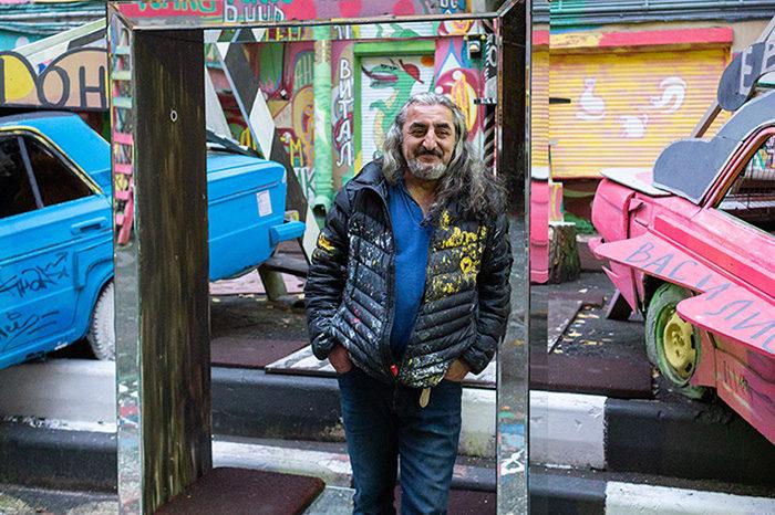 Это бард Нельсон, создавший разноцветный дворик с «Жигулями» на Петроградской. Как он живет в подвале с воронами и пишет песни про космос