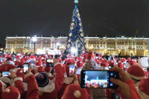 Десятки петербуржцев в костюмах Дедов Морозов пробежали по Дворцовой площади, а на главной елке зажгли огни. Вот как это было