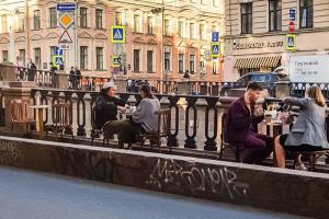 На набережной канала Грибоедова выставили столики, за ними сидят посетители кафе. Теперь по тротуару не пройти