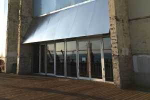 В «Севкабель Порту» заменили двери, выходящие на набережную. Вместо прежних круглых окон-иллюминаторов — панорамные стекла
